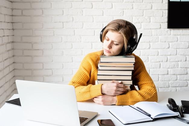 Nauka na odległość. e-learning. młoda kobieta w czarnych słuchawkach do spania na stosie książek