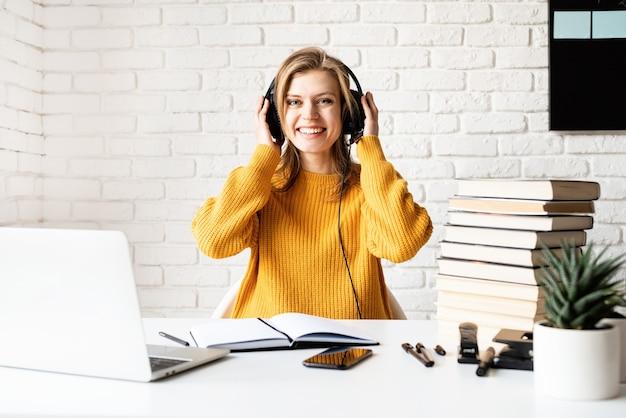Nauka na odległość. e-learning. młoda kobieta w czarnych słuchawkach studiuje online za pomocą laptopa