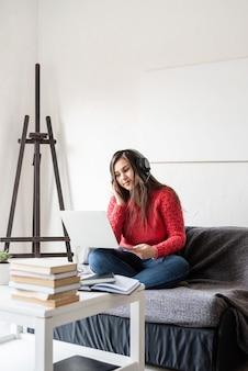 Nauka na odległość. e-learning. młoda kobieta w czerwonym swetrze i czarnych słuchawkach siedzi na kanapie rozmawiając za pomocą laptopa