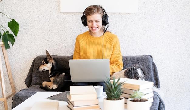 Nauka na odległość. e-learning. młoda uśmiechnięta kobieta w żółtym swetrze i czarnych słuchawkach studiuje online za pomocą laptopa, siedząc na kanapie w domu