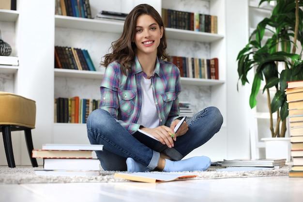 Nauka na odległość. młoda studentka studiująca w domu, pisząca artykuł do publikacji, siedząca na podłodze w przytulnym domowym wnętrzu, otoczona stosem książek