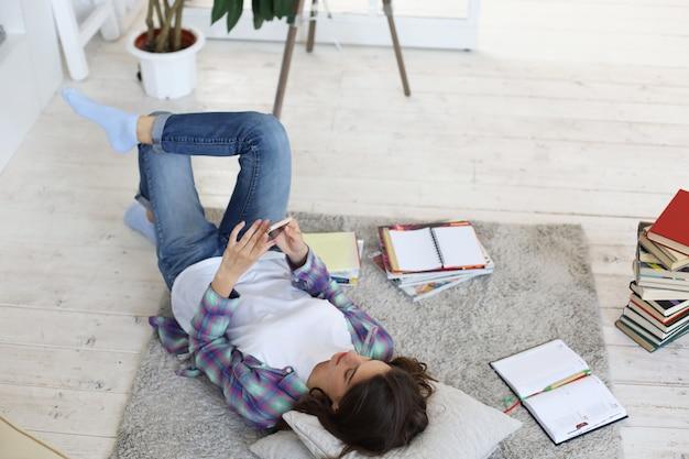 Nauka na odległość. młoda studentka studiująca w domu, przygotowująca się do egzaminów uniwersyteckich, leżąca na podłodze w przytulnym domowym wnętrzu, otoczona stosem książek