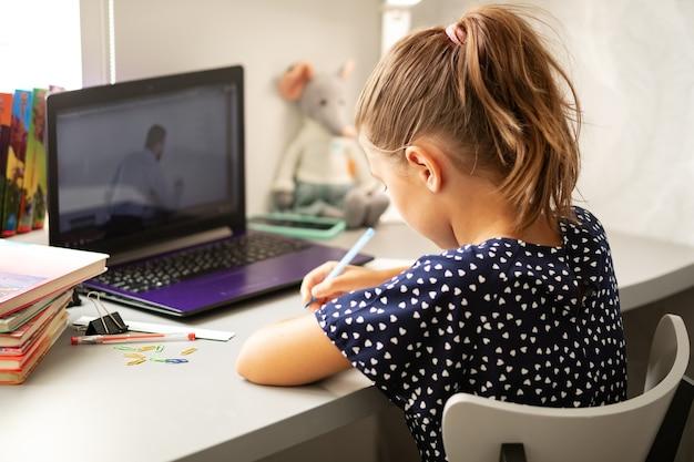 Nauka na odległość online uczennica z komputerem w drodze wideokonferencji komunikuje się z nauczycielem podczas epidemii kwarantanny i koronawirusa