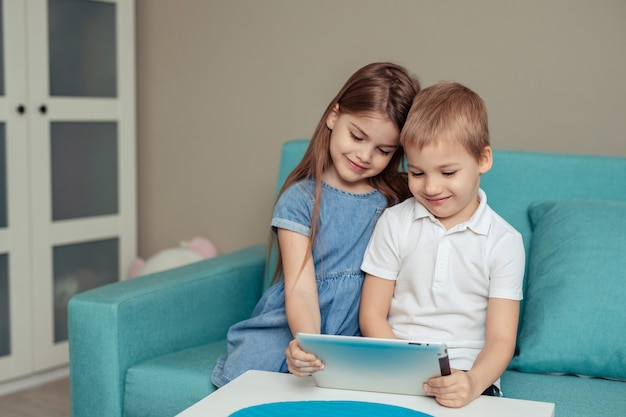 Nauka na odległość w domu w domu. bliźniacy brat i siostra studiują w domu za pomocą tabletu