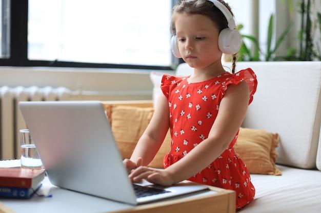 Nauka na odległość. wesoła dziewczynka przy użyciu komputera przenośnego studiując za pośrednictwem systemu e-learningu online.