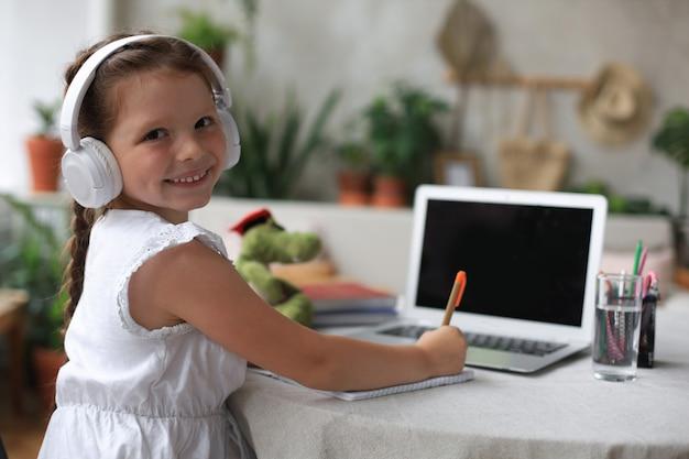 Nauka na odległość. wesoła dziewczynka w słuchawkach za pomocą laptopa studiując za pośrednictwem systemu e-learningu online.