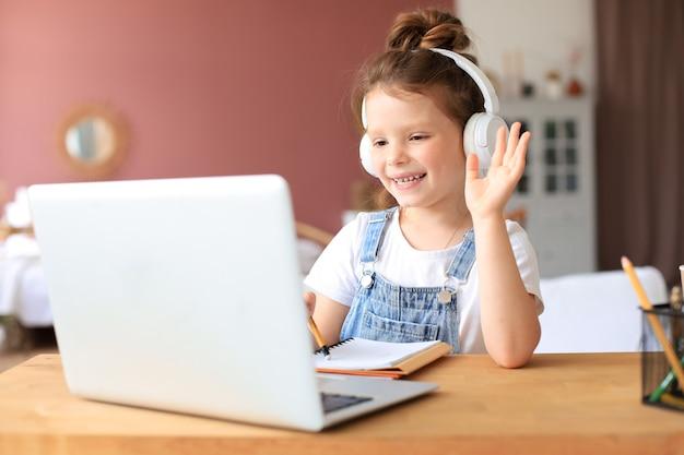 Nauka na odległość. wesoła dziewczynka w słuchawkach za pomocą laptopa studiuje za pośrednictwem systemu e-learningu online.