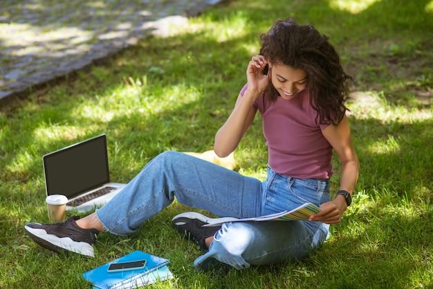 Nauka online. dziewczyna w codziennych ubraniach siedzi na trawie w parku i studiuje