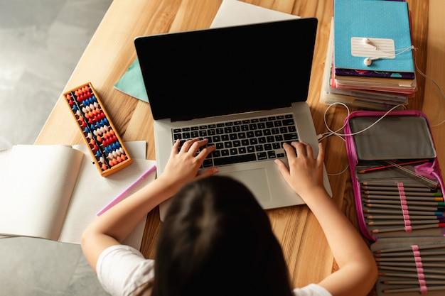 Nauka online. dziewczyna z laptopem odrabia lekcje w domu. uczennica uczy się podczas rozmowy wideo. edukacja na odległość podczas kwarantanny