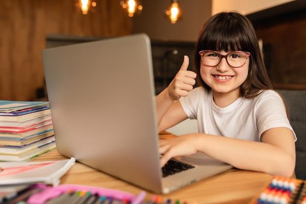 Nauka online. nauczanie domowe. szczęśliwa uczennica odrabia pracę domową za pomocą laptopa w domu. lekcja online z gadżetem cyfrowym. kształcenie na odległość, nauczanie w domu