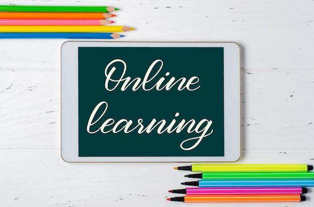 Nauka online - odręczny napis na tablecie. pojęcie szkolenia na odległość dla dzieci. tablet i materiały biurowe na białym tle drewniane.