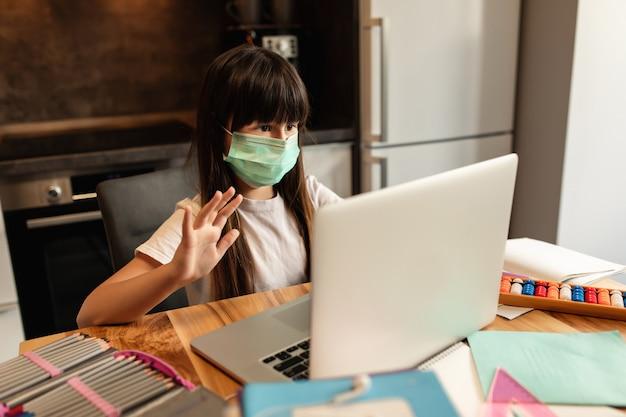 Nauka online podczas kwarantanny. dziewczyna z maską ochronną na twarzy rozmawia z innymi uczestnikami lekcji wideo online. edukacja online w domu.
