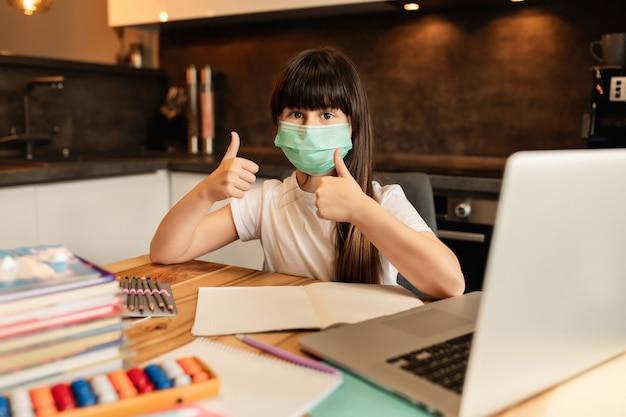 Nauka online podczas kwarantanny. dziewczyna z maską ochronną na twarzy uczy się w domu.
