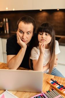 Nauka online. uczennica i jej ojciec oglądają lekcję wideo na laptopie w domu. kształcenie na odległość. rodzinna więź