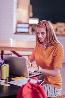 Nauka online. zadowolona rudowłosa dziewczyna pochyla głowę podczas pisania wiadomości na laptopie