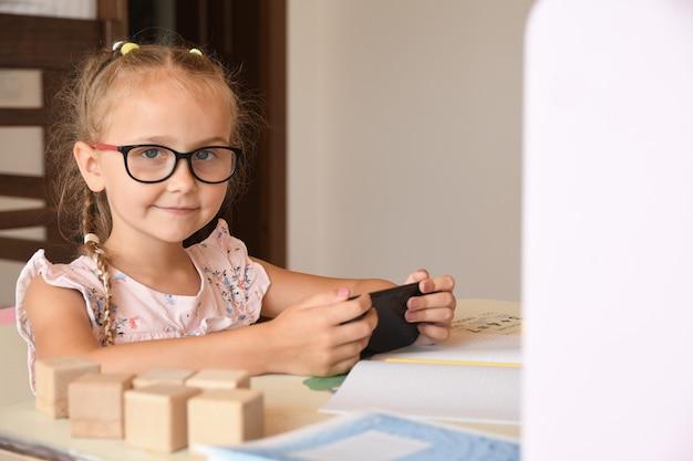Nauka w domu, portret młodej dziewczyny siedzącej przy biurku w okularach, korzystającej ze smartfona, bawi się, uczy się.