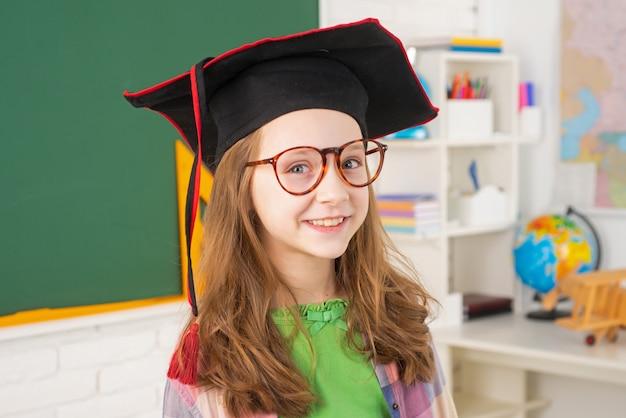 Nauka w szkole podstawowej i koncepcja dzieci mały uczeń w czapce dyplomowej