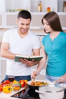 Nauka Wspólnego Gotowania. Szczęśliwa Młoda Para Gotuje Razem W Kuchni, Podczas Gdy Mężczyzna Trzyma Książkę Kucharską Premium Zdjęcia