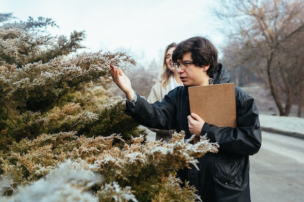 Naukowcy badają gatunki roślin w lesie.