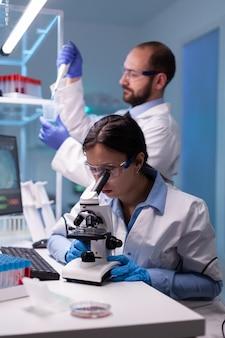 Naukowcy chemicy pracujący w laboratorium z mikropipetą i mikroskopem