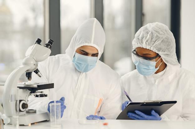 Naukowcy i mikrobiolodzy w kombinezonach ppe i maskach na twarz trzymają probówkę i mikroskop w laboratorium, szukając leczenia lub szczepionki na infekcję koronawirusem. covid-19, koncepcja laboratorium i szczepionki.