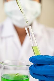 Naukowcy noszą maski i rękawiczki, niosąc zlewki ze szczepionkami.