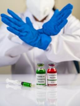 Naukowcy noszą niebieskie rękawiczki i robią ręce nieakceptowalną szczepionkę, aby zapobiec covid-19