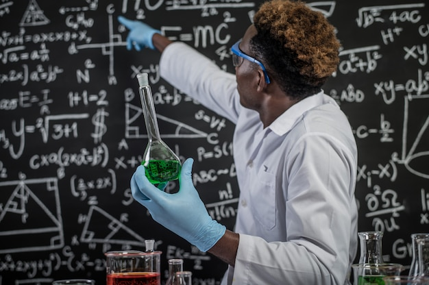 Naukowcy noszą okulary trzymające zielone chemikalia i wskazują na formułę na tablicy
