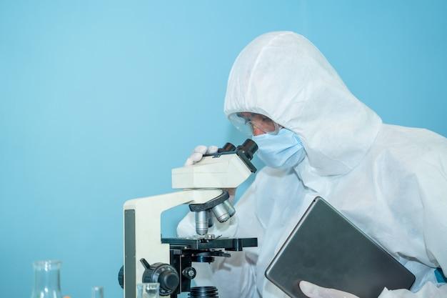Naukowcy pracujący w laboratorium, z bliska lekarze w odzieży ochronnej hazmat ppe noszą gumowe rękawice medyczne używają mikroskopu w laboratorium.