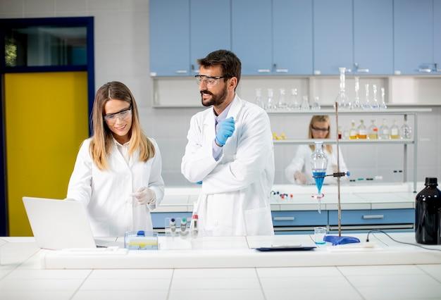 Naukowcy pracujący z niebieskim płynem w lejku rozdzielającym w laboratorium