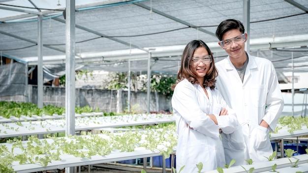 Naukowcy stoją w hydroponicznej farmie rolników, gdzie uprawiają ekologiczną sałatę warzywną i sałatę