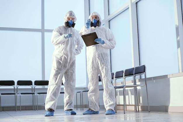 Naukowcy w kombinezonach ochronnych rozmawiają o czymś stojącym w laboratorium