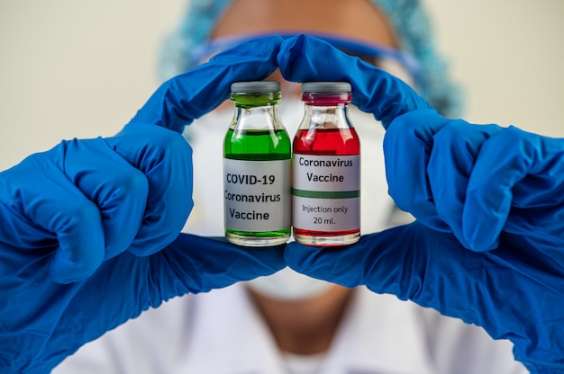 Naukowcy w maskach i rękawiczkach, niosący fiolki ze szczepionkami w celu ochrony covid-19