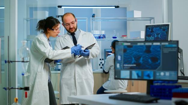 Naukowcy współpracownicy korzystający z cyfrowego tabletu pracujący w medycznym laboratorium badawczym, analizujący próbki biochemiczne, rozmawiający. laboratorium naukowe dla medycyny, rozwój mikrobiologii z zaawansowanym sprzętem