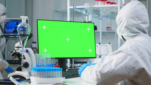 Naukowiec człowiek ubrany w kombinezon ochronny pisania na komputerze z zielonym makieta w nowocześnie wyposażonym laboratorium. zespół mikrobiologów prowadzących badania nad szczepionkami piszący na urządzeniu z kluczem chrominancji, izolowany wyświetlacz.