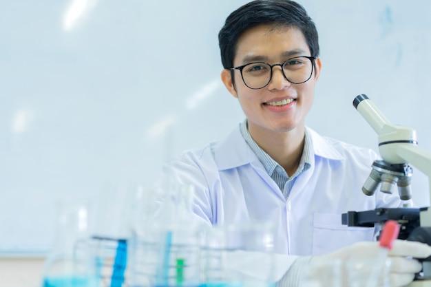 Naukowiec człowiek z mikroskopem na biurku w sali laboratoryjnej dla koncepcji badań