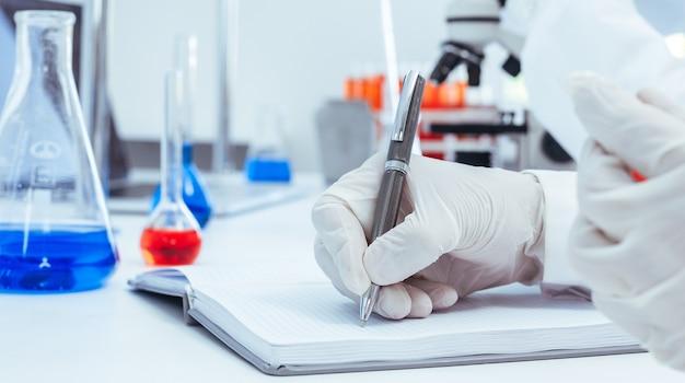 Naukowiec dokonujący wpisu w czasopiśmie laboratoryjnym.