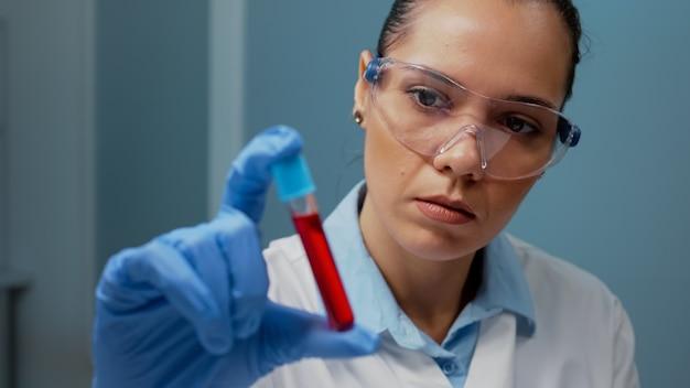 Naukowiec laboratoryjny trzymający vacutainer z próbką krwi