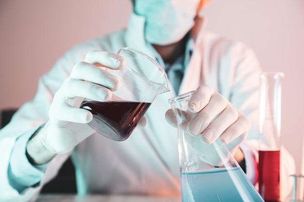 Naukowiec lub lekarz w fartuchu laboratoryjnym, trzymając probówkę
