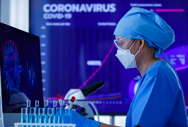 Naukowiec lub naukowiec trzymający probówkę do badania krwi covid-19 i pracujący z ekranem komputera do analizy i badania nad koronawirusem w laboratorium.
