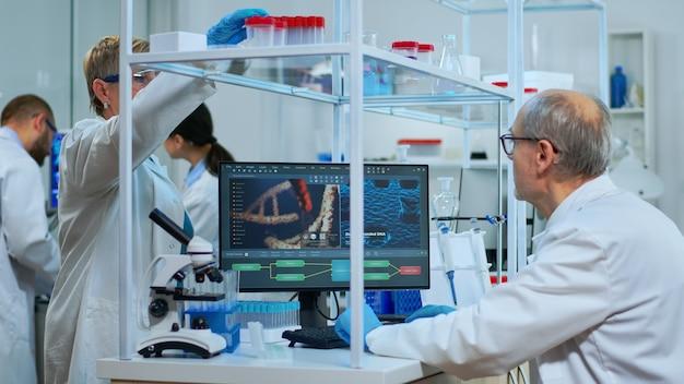 Naukowiec medyczny pracujący z obrazem skanowania dna w nowocześnie wyposażonym laboratorium. wieloetniczny zespół badający ewolucję szczepionek przy użyciu zaawansowanych technologicznie i chemicznych narzędzi do badań naukowych i opracowywania wirusów