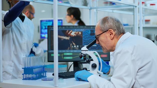 Naukowiec medyczny prowadzący eksperymenty dna pod mikroskopem w nowocześnie wyposażonym laboratorium. wieloetniczny zespół badający ewolucję wirusa przy użyciu zaawansowanych technologii do opracowania szczepionki przeciwko covid19