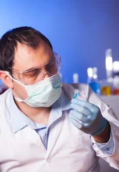 Naukowiec myśli o badaniach i trzymaniu probówki eppendorfa