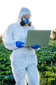 Naukowiec na sobie białą maskę chemiczną sprzętu ochronnego pole farmy laptopa