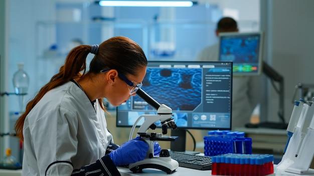 Naukowiec oglądający próbki biologiczne pod mikroskopem piszący na komputerze. zespół chemików pracujących w laboratorium, badający ewolucję wirusa przy użyciu zaawansowanych technologii do badań naukowych nad rozwojem szczepionek.