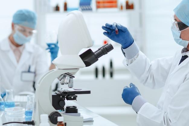 Naukowiec otwierający ampułkę z nową szczepionką