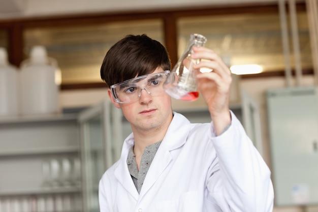 Naukowiec patrząc na cieczy w kolbie erlenmeyera