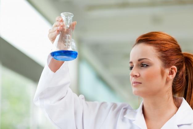 Naukowiec patrząc na niebieski płyn