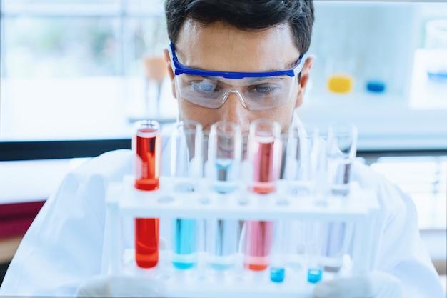 Naukowiec patrzeje badanie medyczne w szklanej tubce podczas gdy robić badaniu w naukowym laboratorium
