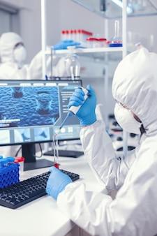 Naukowiec pobierający próbkę krwi z probówki za pomocą mikropipety. lekarz pracujący z różnymi bakteriami i tkankami, badania farmaceutyczne nad antybiotykami przeciwko covid19.